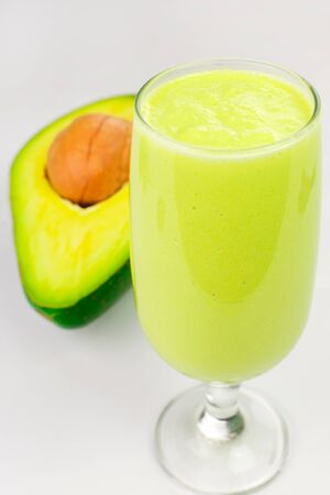 Glass of avocade cream with an open avocade isolated in white background