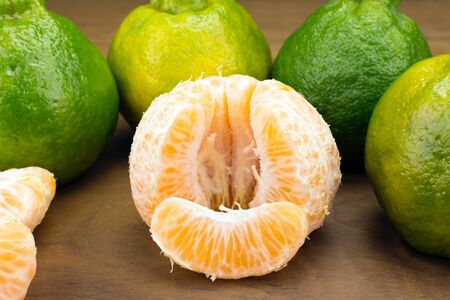 Tangerine variety typical in brazil called ponkan with one peeled isolated in wood background