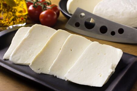 Slices of buffalo fresh cheese made in Serra da Canastra, in a platter in wood background Imagens