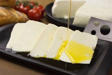 Pouring olive oil in slices of buffalo fresh cheese made in Serra da Canastra, in a platter in wood background