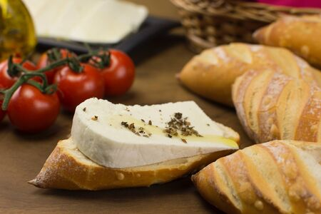 Slice of buffalo fresh cheese made in Serra da Canastra, in Italian bread in wood background