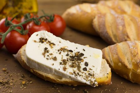 Slice of buffalo fresh cheese made in Serra da Canastra, in Italian bread in wood background close Stock Photo