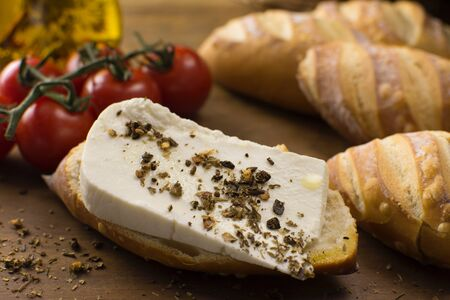 Slice of buffalo fresh cheese made in Serra da Canastra, in Italian bread in wood background close in half light