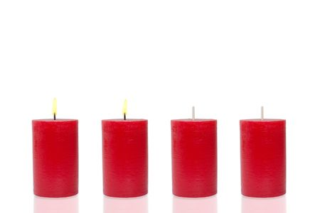 Four red candles before white background,two burn photo