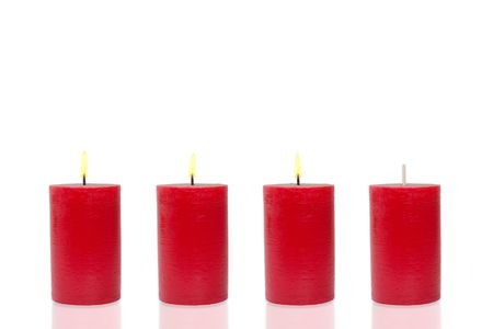 Four red candles before white background, three burn photo