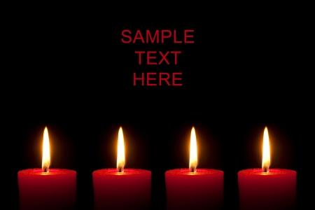 corona de adviento: Cuatro velas rojos ardientes delante de fondo negro