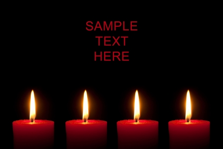 four objects: Four burning red candles in front of black background