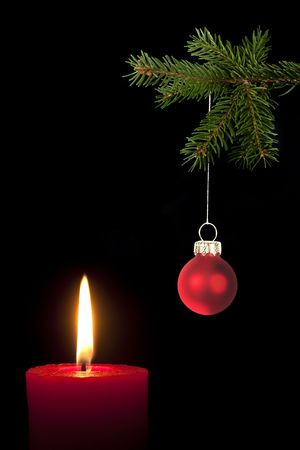 Fir branch with Christmas tree ball and red candle in front of black background Stock Photo - 5815655