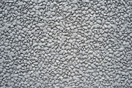 steadily: Grey painted pebble stones on a wall as a background motive