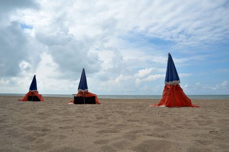 sunshades: Beach in cold weather, with three closed sunshades Stock Photo