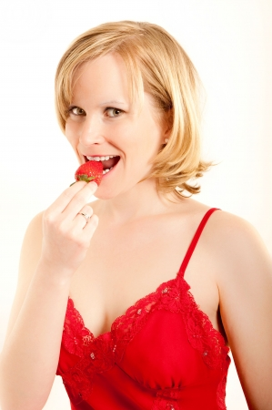 erotical: Pretty young woman bites in a fresh strawberry