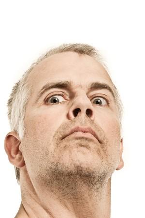 Unshaven man with crazy expression looking down Standard-Bild