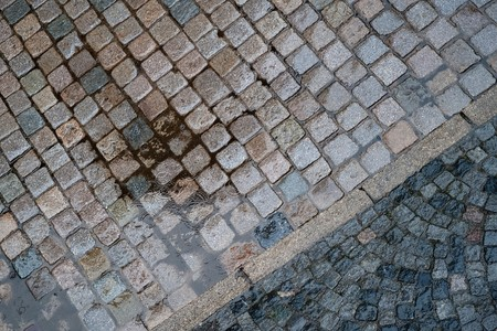 spoted: Raindrops are falling in a puddle on a paved street Stock Photo