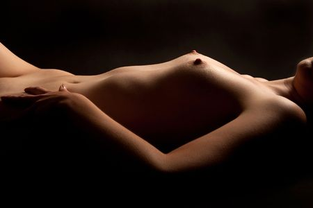 naked  body: Naked torso of a beautiful young woman, recumbent in front of black background