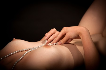 small breast: Sexy young woman playing with a pearl necklace between her breasts Stock Photo