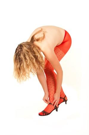 bending down: Joven y bella mujer en pantimedias rojos plegado hacia abajo a sus zapatos
