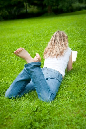 Beautiful young curly blond woman reading a book in a park