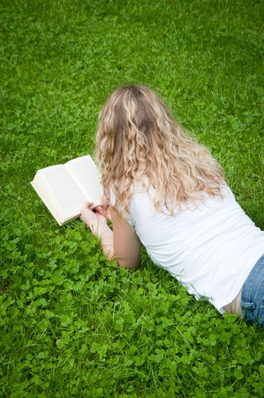 Beautiful young curly blond woman reading a book in a park photo