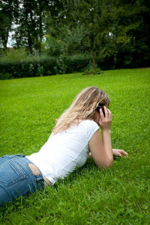 Beautiful young curly blond woman  telephoning in a park Stock Photo - 7681119