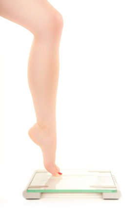 Slender leg of a woman fearing weight scale photo