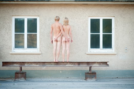 Nude of a young couple, rear view in front of a house facade