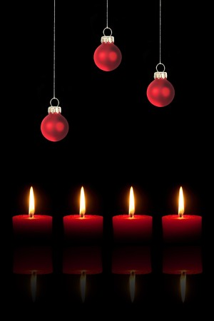 Three red Christmas tree balls and four red candles on black background  photo