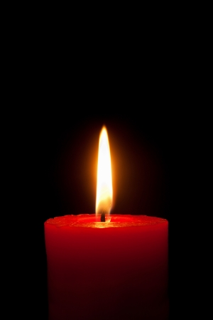 A single burning red candle  isolated in front of black background Standard-Bild