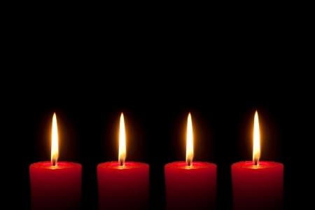 corona de adviento: Cuatro velas rojas ardientes delante de fondo negro