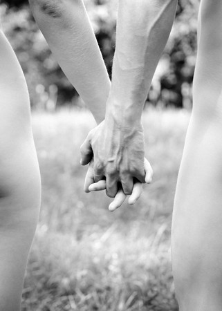 Naked young couple walking hand in hand in nature,  black and white, little grain added photo