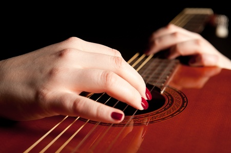 Fingers of a young woman playing guitar, closeup photo