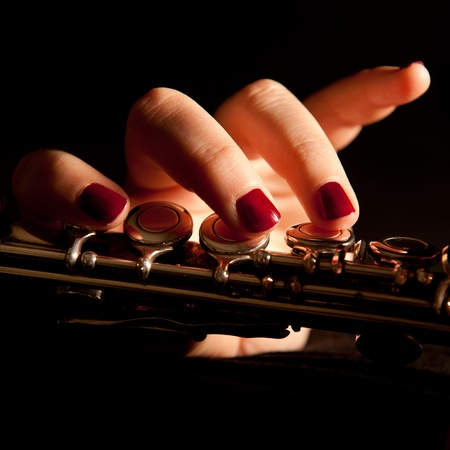 Fingers of a young woman playing transverse flute, closeup  Stock Photo