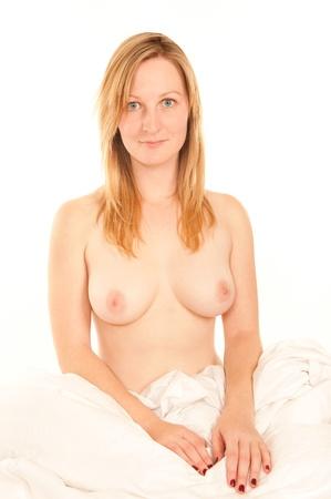 mujer desnuda sentada: Sexy mujer desnuda sentada en la cama, de fondo blanco  Foto de archivo