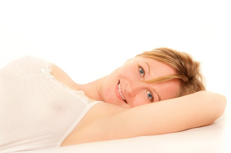 Portrait of a sexy young woman wearing white nightdress lying in bed  photo