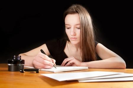 persona escribiendo: Bastante joven mujer escribiendo una carta a la mesa de una vieja Foto de archivo