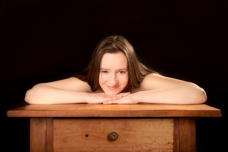 erotically: Portrait of a beautiful  woman bending over an old wooden table