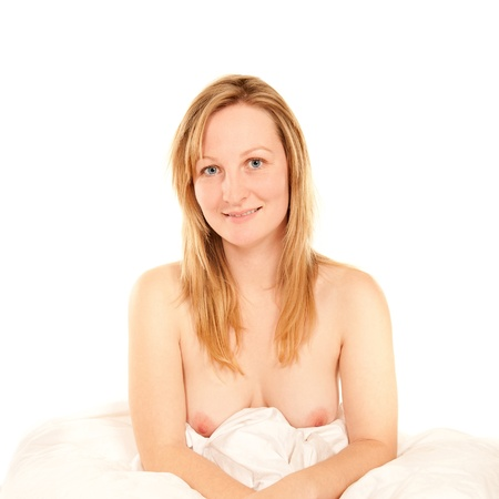 Portrait of a beautiful topless blond woman sitting in bed  photo