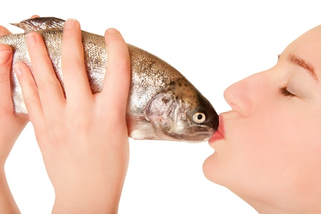Beautiful young woman with closed eyes kissing a fish, isolated on white photo