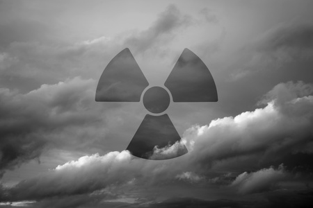 Dramatic sky with symbol of radioactivity as a background motive, monochrome  photo