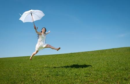 salto largo: Joven y bella mujer saltando con paraguas blanco bajo cielo azul