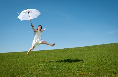 Beautiful young woman jumping with white umbrella under blue sky Standard-Bild