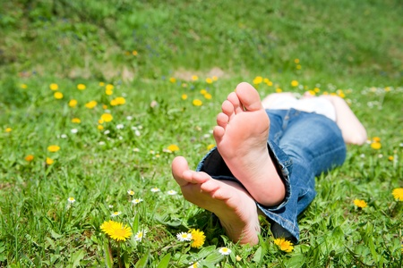 Feet of a beautiful young woman lying in a meadow with many colorful flowers in spring