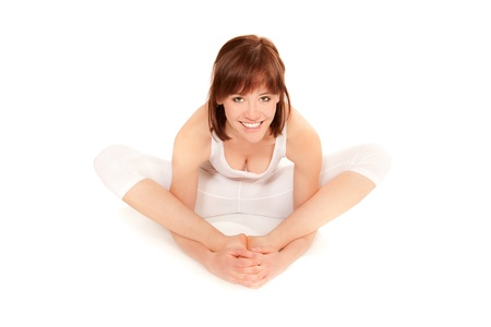 Young athletic woman doing yoga exercise in white sportswear, in front of white background photo