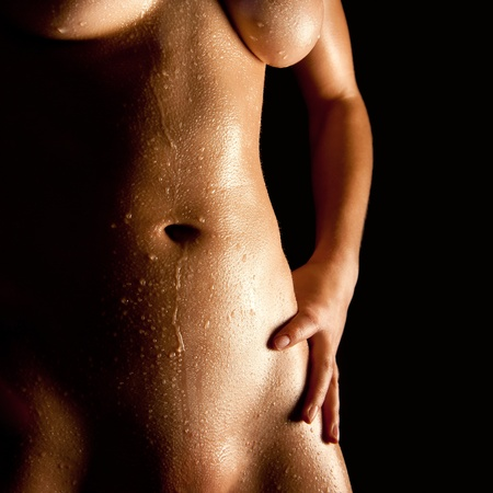 Wet body of a nude young woman in front of black background