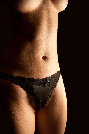 Wet body of a sexy young woman in beautiful black panties in front of black background