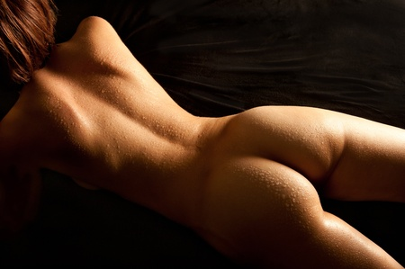 Beautiful back of nude young woman with wet body lying on black mattress