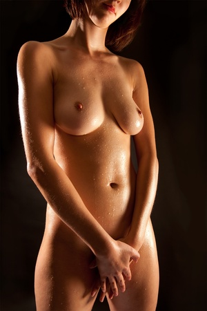 Closeup of a beautiful nude womans torso in front of black background