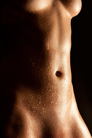 Wet abdomen of a nude young woman in front of black background Stock Photo