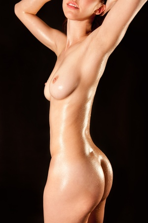 Closeup of a nude wet female torso in front of black background Stock Photo