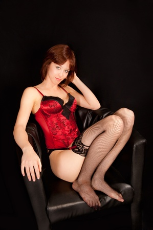 Portrait of a beautiful woman in erotic underwear sitting in black armchair Stock Photo - 9383604