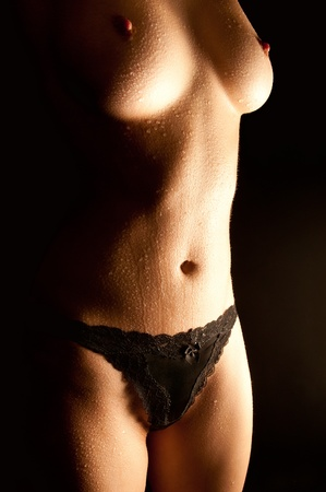 Wet body of a sexy young woman in beautiful black panties in front of black background Stock Photo - 9392968